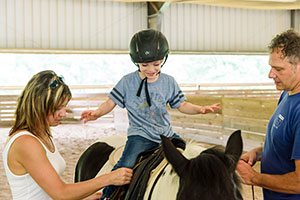 CSD student Michelle Forrest and clinical instructor Perry Flynn help a camper mount a horse. Horsepower Experience combines horseback riding and speech therapy in a camp experience.