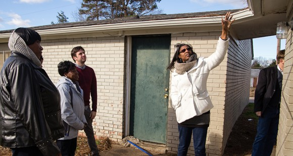 Josie Williams of the Greensboro Housing Coalition walks a group through the Cottage Grove neighborhood, pointing out issues that can lead to health problems. [Photo by Mike Dickens]