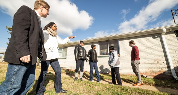 CHCS Director Stephen Sills and Josie Williams of the Greensboro Housing Coalition walk a group through the Cottage Grove neighborhood, pointing out issues that can lead to health problems. [Photo by Mike Dickens]